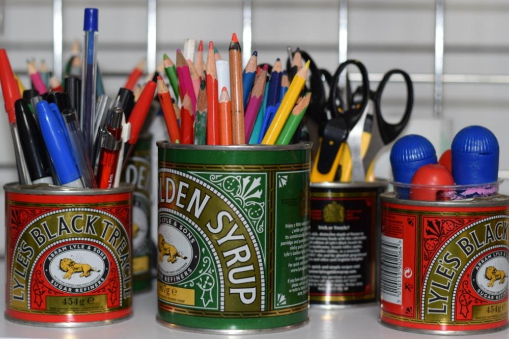 printmaking tools, crayons, pencils in tins in Barley Barn, Essex