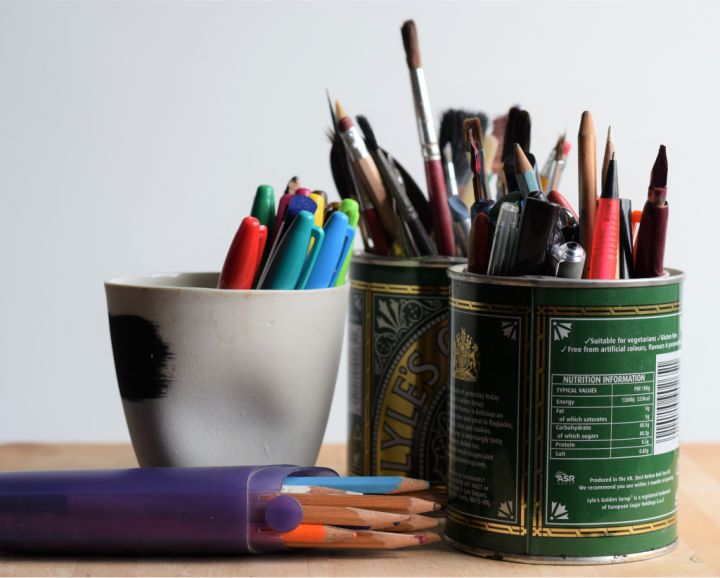 Paintbrushes, pens, pencils in pots in artist's studio