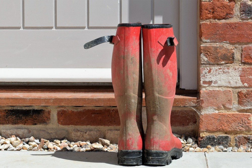 Mud spattered boots in front of door