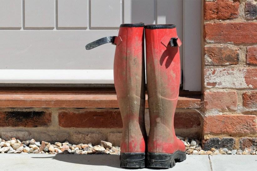Mud spattered boots in front of door
