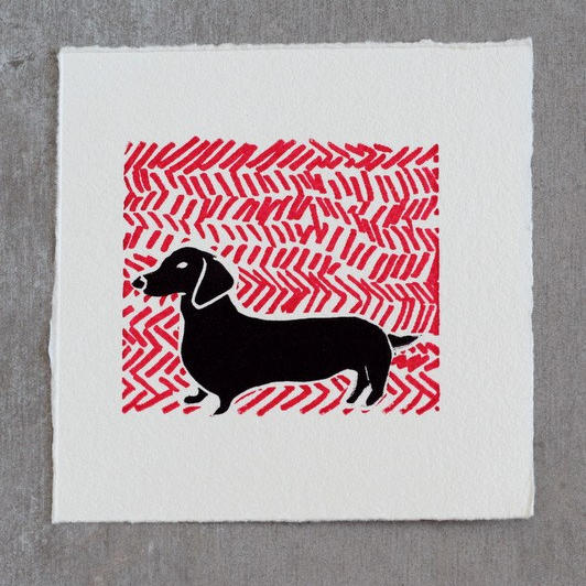 Hugo the sausage dog lino print on screen printed background.