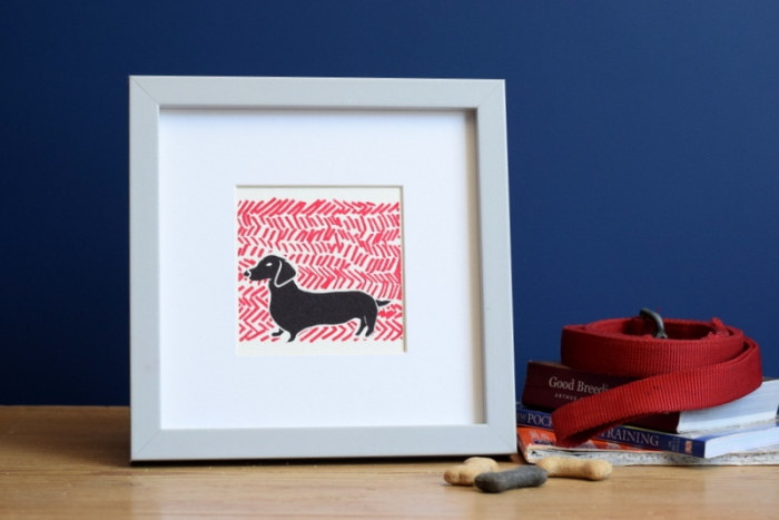 Sausage dog lino print on raspberry coloured background by Ruth Wheaton