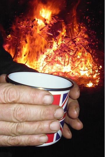 A mug of Slamseys Sloe Gin Winter Warmer in front of the bonfire