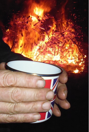 A mug of Slamseys Sloe Gin Winter Warmer in front of the bonfire