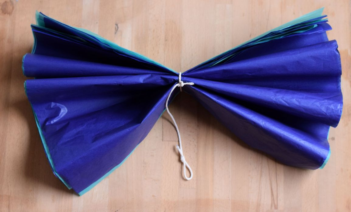 To make paper pom poms tie the string around the paper and fan out