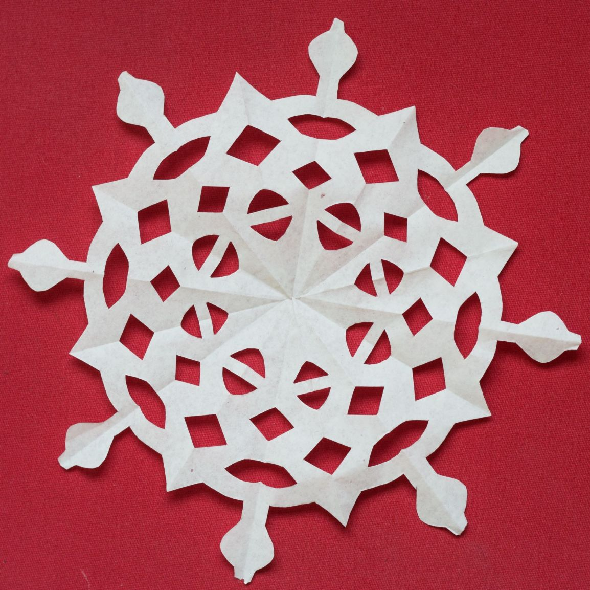 Flat paper snowflake red background