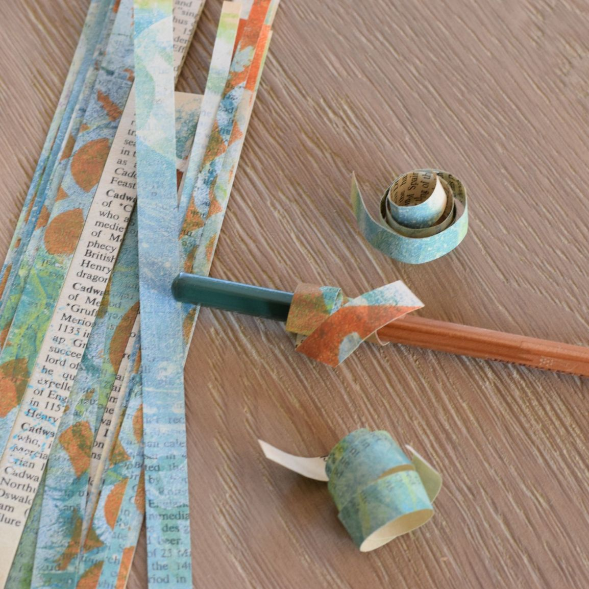 Winding strips of paper around a pencil to make paper filled Christmas baubles