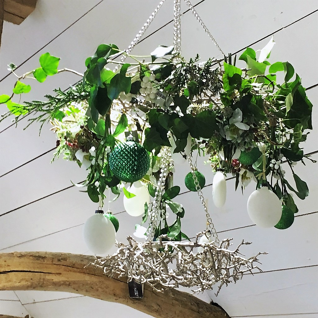 Christmas chandelier of faux and natural foliage with baubles