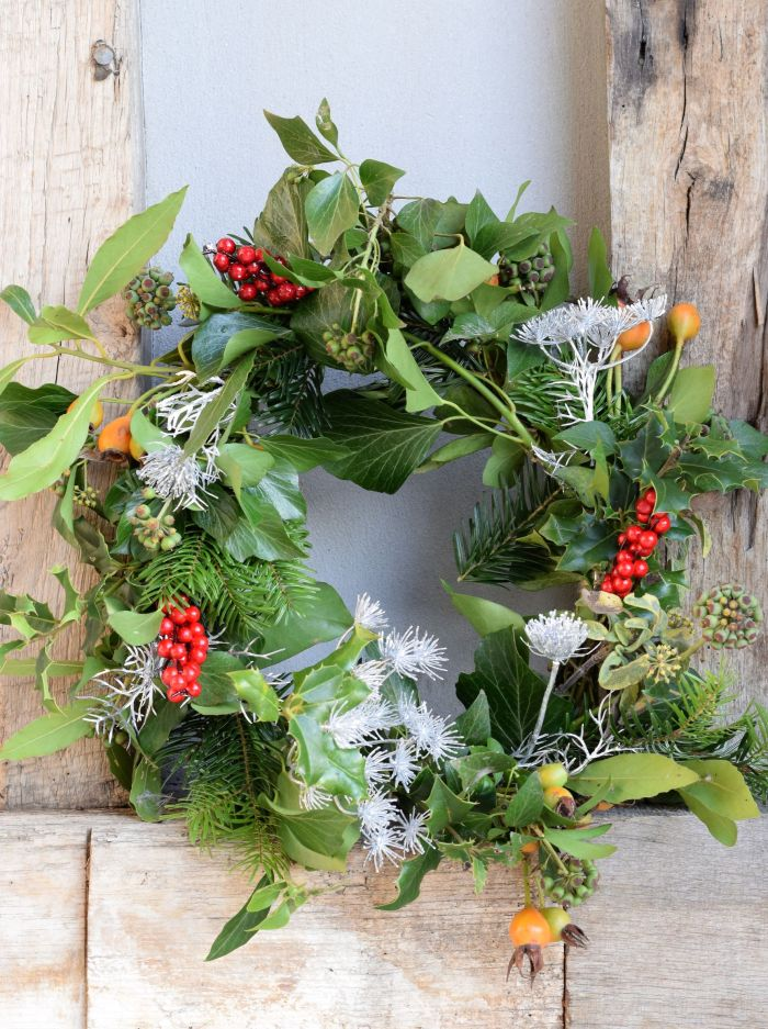Rustic evergreen Christmas wreath with rosehips and faux berries and cow parsle