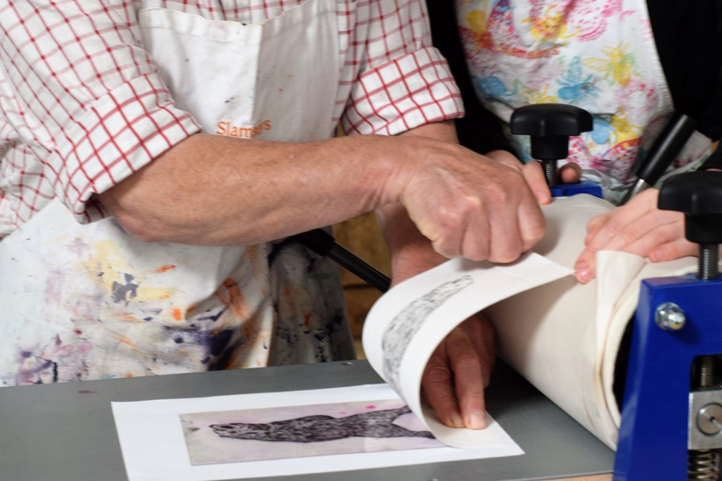man revealing drypoint print by etching press