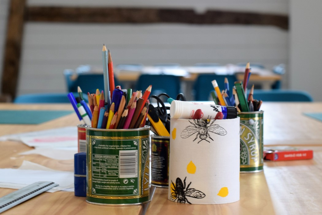 Pencils stored in tins on work table in printmaking space