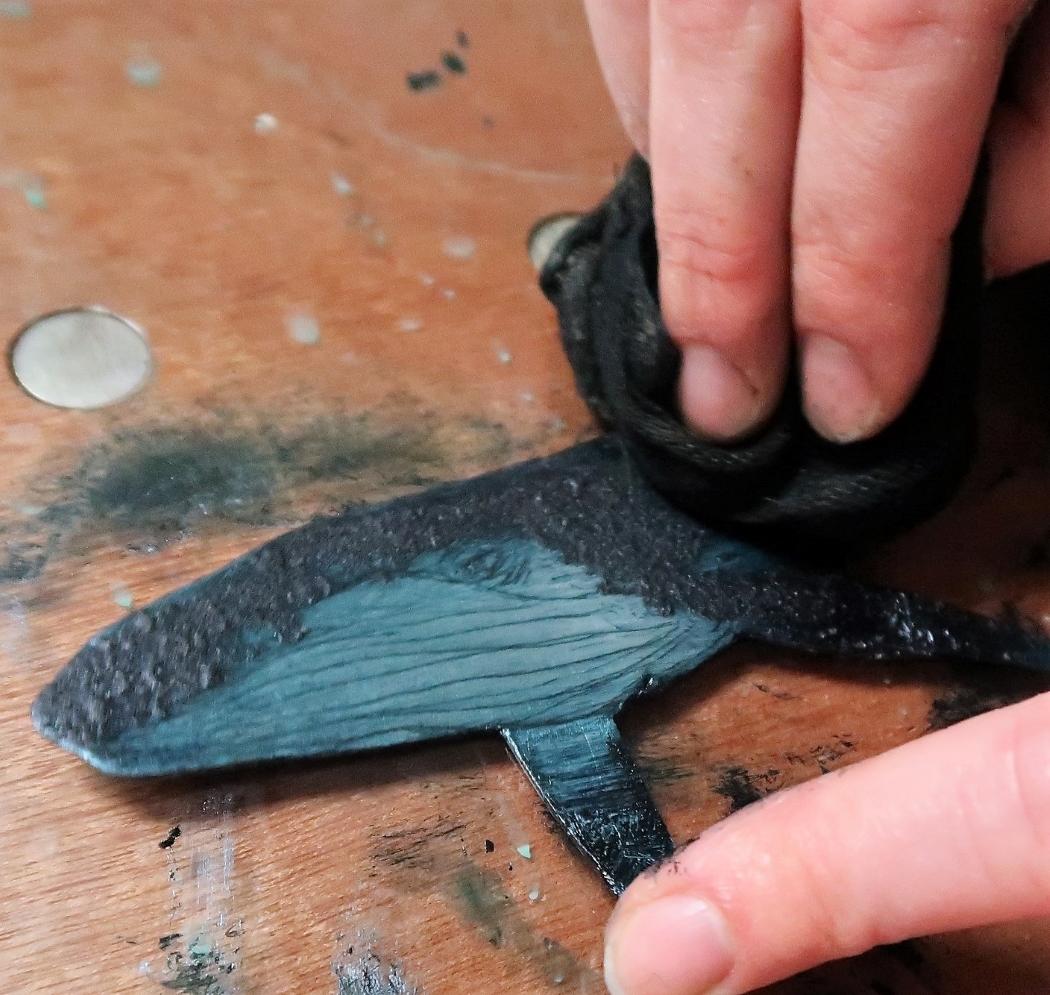 Printmaker removing ink from aluminium plate