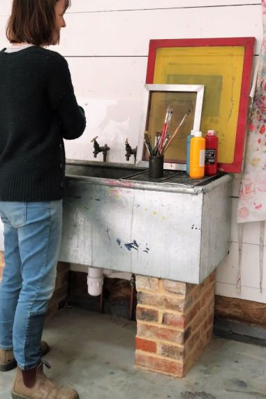 Printmaker washing out at sink in print studio