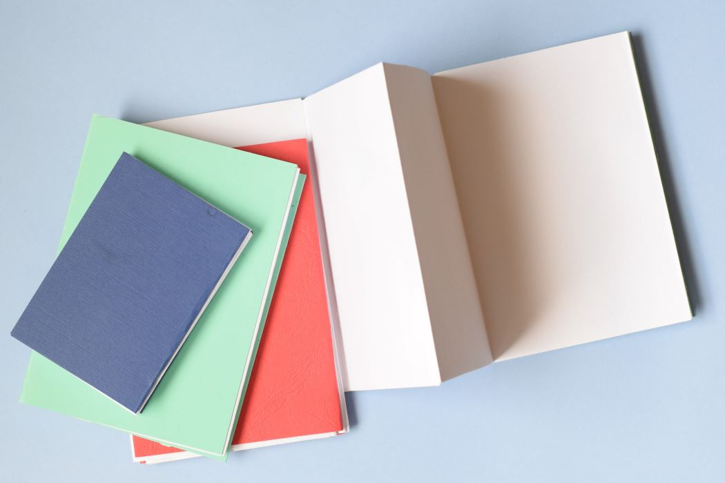 3 closed and one open concertina notebooks with soft covers