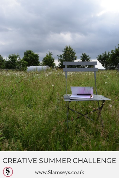 creative summer challenge text below chair with sketchbook in field with ox-eye daisies