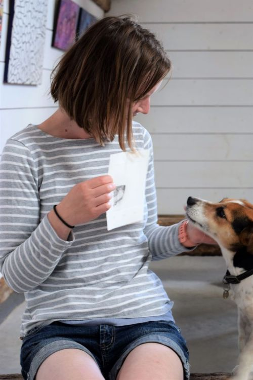 woman holding up print of dog's nose next to Jack Russel terrier with pictures on wall behind