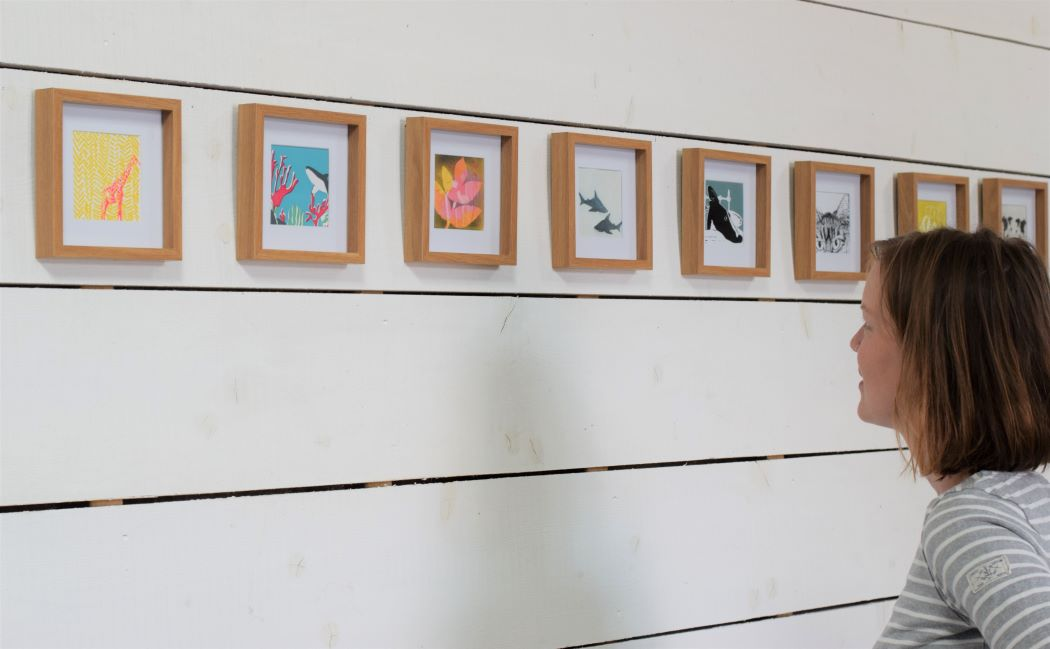 woman looking at framed prints on white boarded wall
