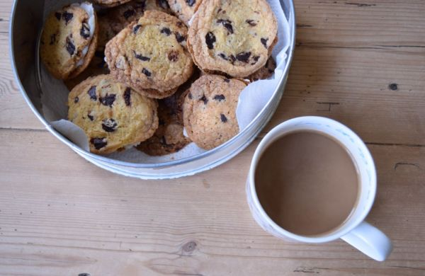 mug of coffee with tin of homemade biscuits