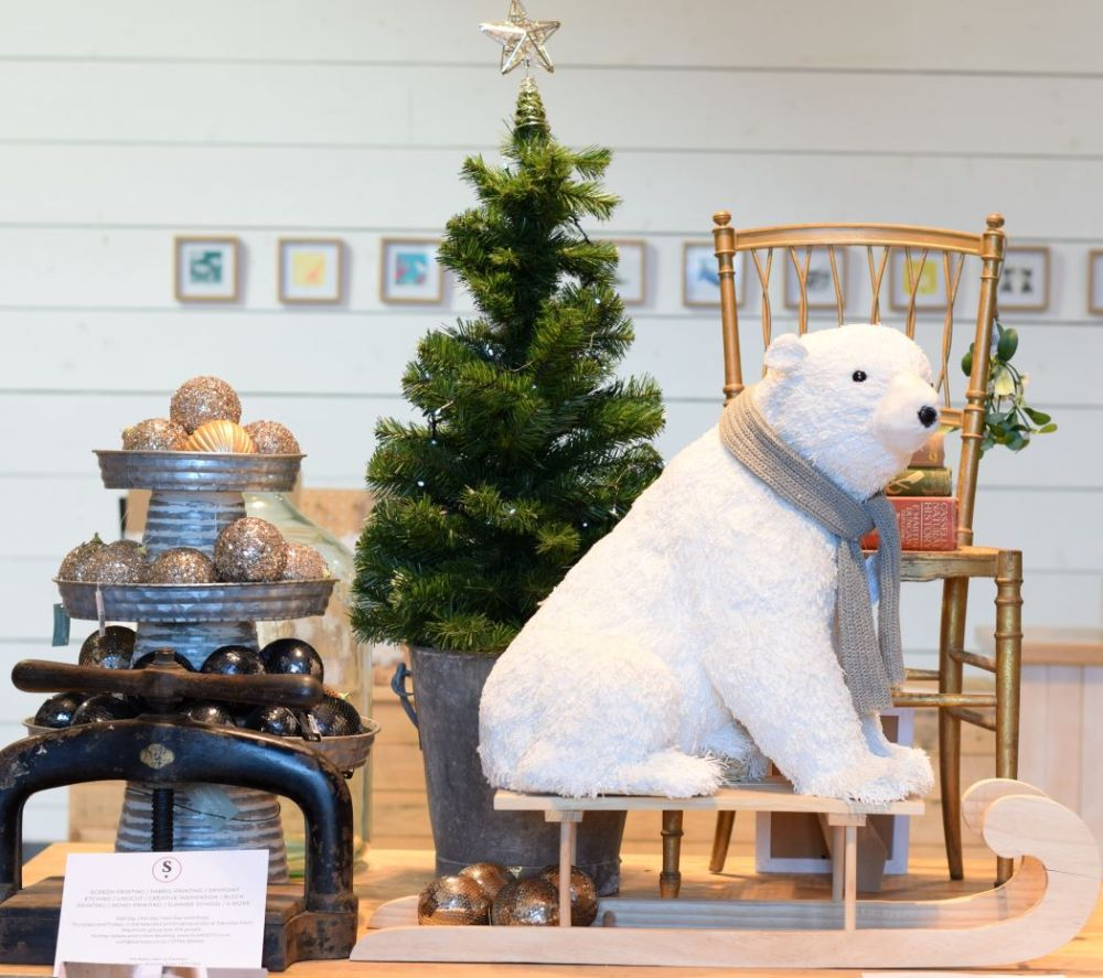 Baubles, Christmas tree, chair with books, toy polar bear on sledge, printing press
