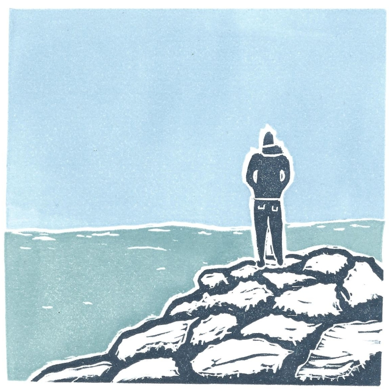 Lino print of lone figure on rocks looking to sea