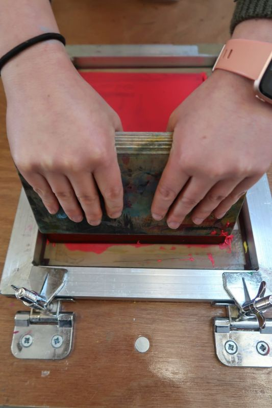 Using a squeegee to push ink through screen to make screen print