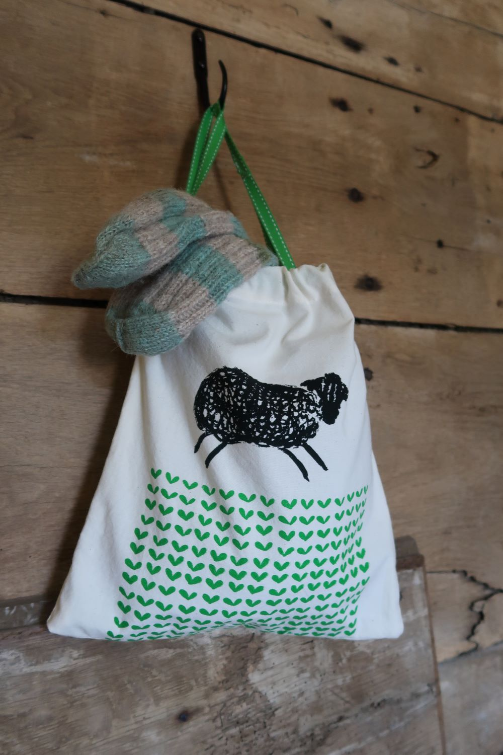 Screen printed jolly sheep and green field on drawstring bag